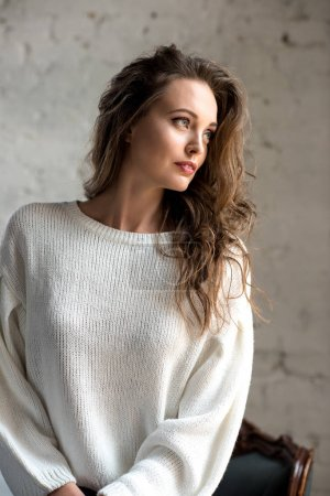 portrait of beautiful young brunette girl in trendy white sweater looking away