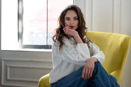 Photo for Beautiful brunette woman in white sweater and jeans sitting on armchair and looking at camera - Royalty Free Image