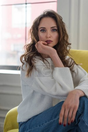 portrait of tender brunette girl in white sweater and jeans sitting on armchair and looking at camera