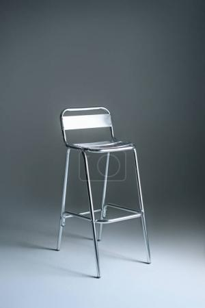 single empty metallic stool on grey