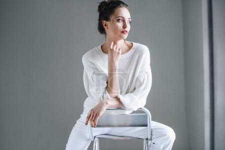 portrait of beautiful brunette woman in trendy white clothes sitting on chair and looking away on grey