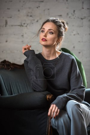Photo for Attractive brunette woman in trendy jumper sitting on armchair and looking away - Royalty Free Image