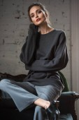 beautiful tender girl in grey jumper and pants sitting on armchair and looking at camera