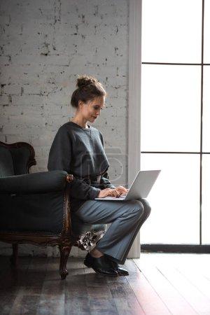 Photo pour Vue de la pleine longueur de belle femme élégante souriante utilisant l'ordinateur portable assis sur fauteuil - image libre de droit