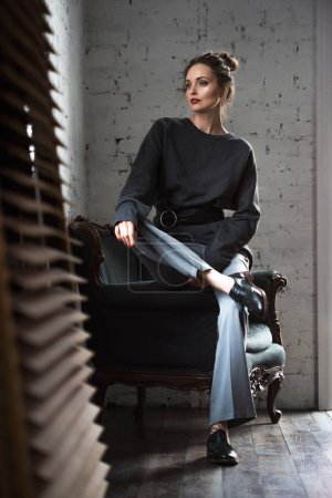 full length view of stylish young woman sitting on armchair and looking away indoors