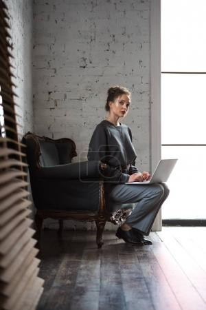 Photo for Full length view of beautiful stylish woman using laptop and looking at camera while sitting on armchair - Royalty Free Image