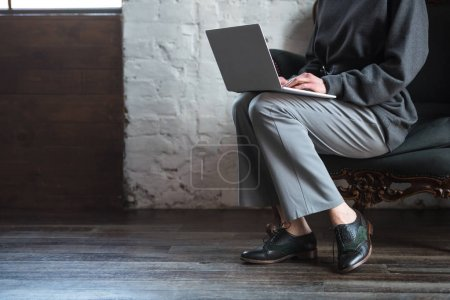 cropped shot of girl in grey clothes and stylish shoes using laptop