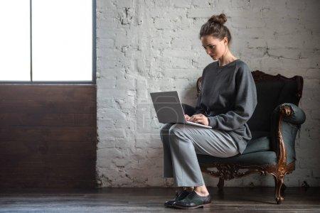 Photo pour Vue pleine longueur de belle jeune femme élégante en utilisant un ordinateur portable à l'intérieur - image libre de droit