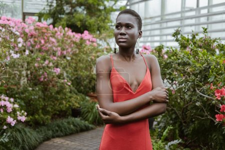 beautiful african american girl with short hair in red dress posing in garden with flowers