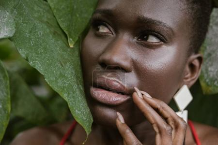 frightened african american girl posing in green garden