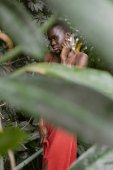 selective focus of young fashionable african american girl posing in tropical garden
