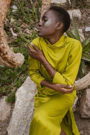 Photo pour Offres femme afro-américaine avec les yeux fermés et paillettes maquillage posant dans jardin tropical - image libre de droit