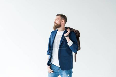 Handsome man in casual clothes with backpack looking away isolated on light background