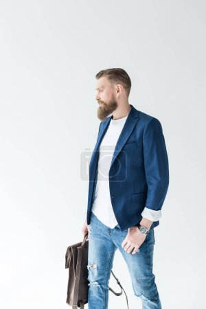 Handsome man in casual clothes holding backpack isolated on light background