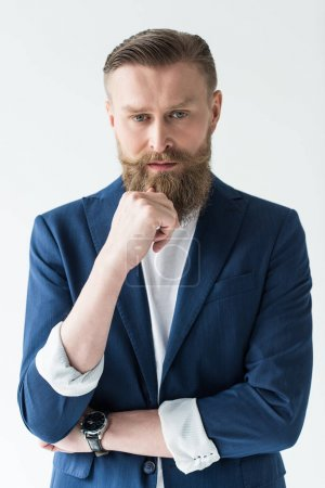 Handsome man in casual clothes with hand near beard isolated on light background