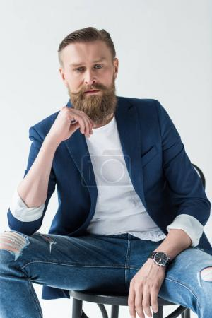 Stylish bearded man sitting on chair isolated on light background