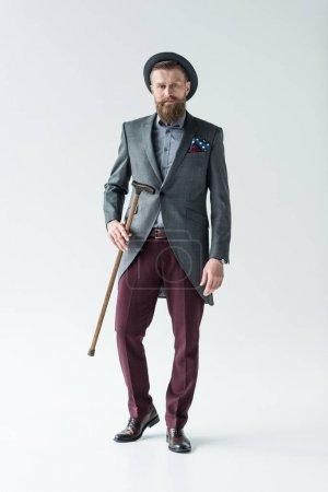 Stylish bearded man holding cane on light background