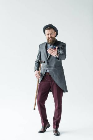 Man with vintage mustache and beard holding cane and reaching with hand