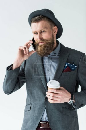 Handsome businessman in vintage style clothes holding paper cup and talking on phone isolated on light background
