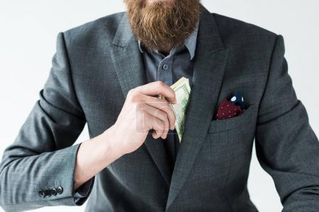 Cropped view of bearded man getting money out of pocket isolated on light background