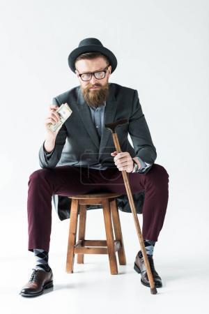 Stylish bearded businessman holding dollars and cane while sitting on stool