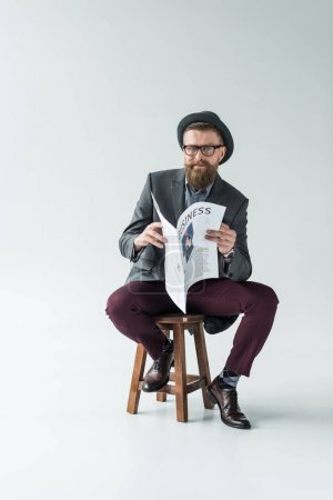 Businessman with vintage mustache and beard reading business newspaper while sitting on stool
