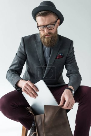Handsome businessman in vintage style clothes with laptop and backpack isolated on light background