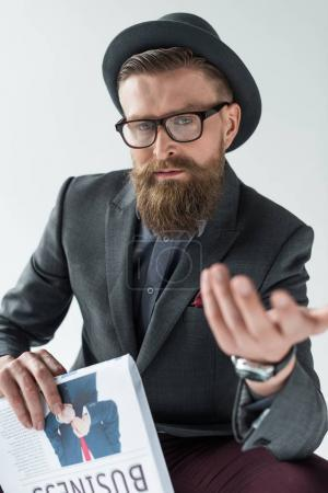 Stylish bearded businessman holding newspaper and gesturing isolated on light background