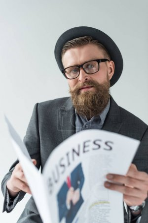 Businessman with vintage mustache and beard reading business newspaper isolated on light background