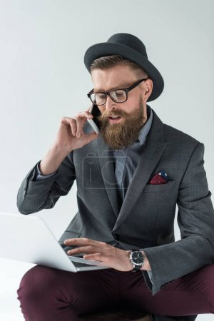 Businessman with vintage mustache and beard talking on smartphone and working on laptop isolated on light background