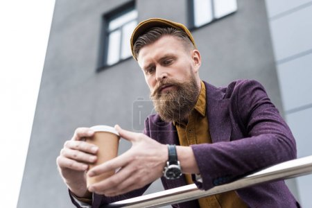 Businessman with vintage mustache and beard holding coffee cup on street