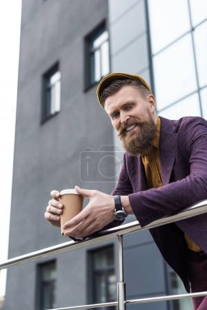 Handsome businessman in vintage style clothes smiling and holding coffee cup