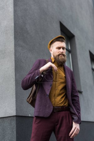 Stylish bearded man with backpack standing on street