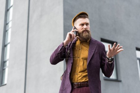 Handsome man in vintage style clothes talking on smartphone