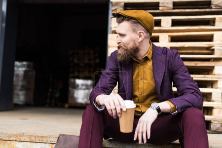 Stylish bearded businessman sitting on street with paper cup in hands