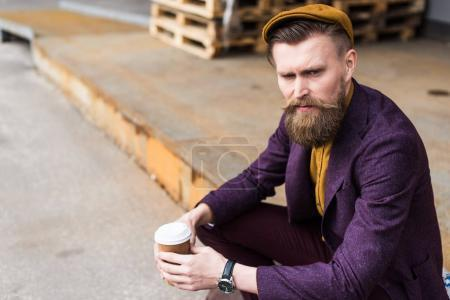 Handsome businessman in vintage style clothes sitting on street with paper cup in hands