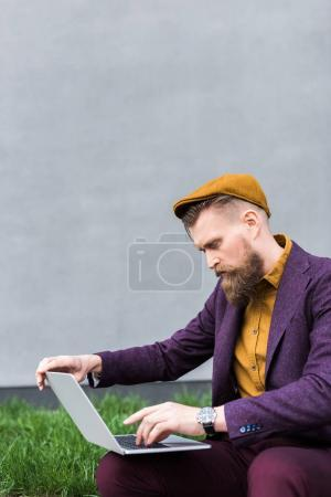 Businessman with vintage mustache and beard sitting on street and looking at laptop