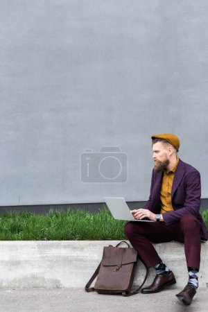 Businessman with vintage mustache and beard working on laptop by building