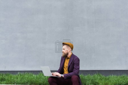 Handsome businessman in vintage style clothes working on laptop