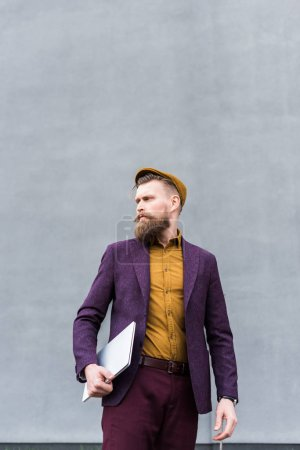 Businessman with vintage mustache and beard holding laptop