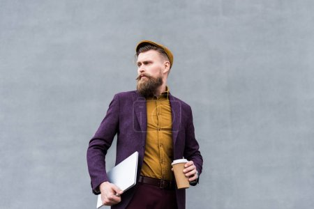 Handsome businessman in vintage style clothes holding laptop and paper cup