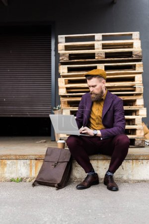 Handsome businessman in vintage style clothes typing on laptop keyboard