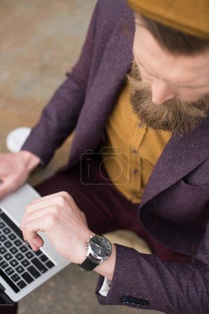 Businessman with vintage mustache and beard working on laptop and checking his watch