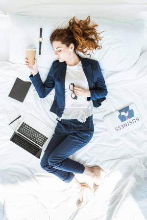 Top view of businesswoman in suit holding coffee cup and sleeping in bed among folders and documents