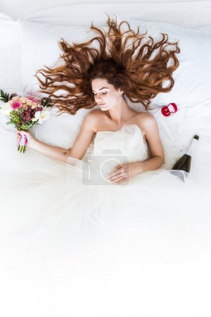 Photo for Top view of young girl in wedding dress sleeping in bed with flowers and wedding rings - Royalty Free Image