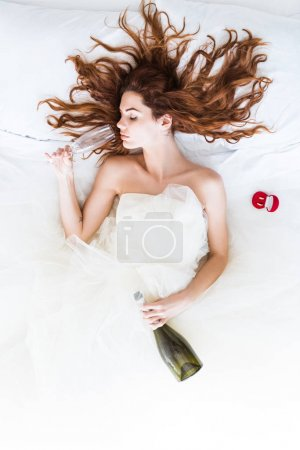 Top view of bride wearing white dress lying in bed and drinking champagne