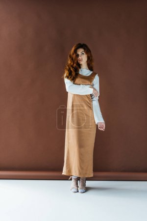 Attractive redhead woman standing on brown background