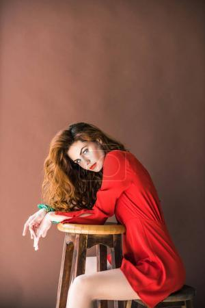 Woman with long red hair sitting on chair by stool isolated on brown background