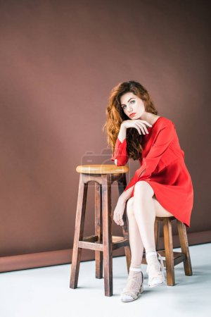 Attractive redhead woman sitting on chair by tall stool