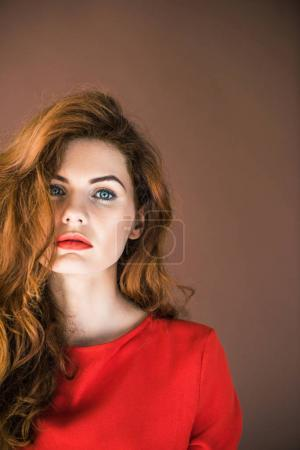 Photo for Woman with long red hair looking at camera isolated on brown background - Royalty Free Image